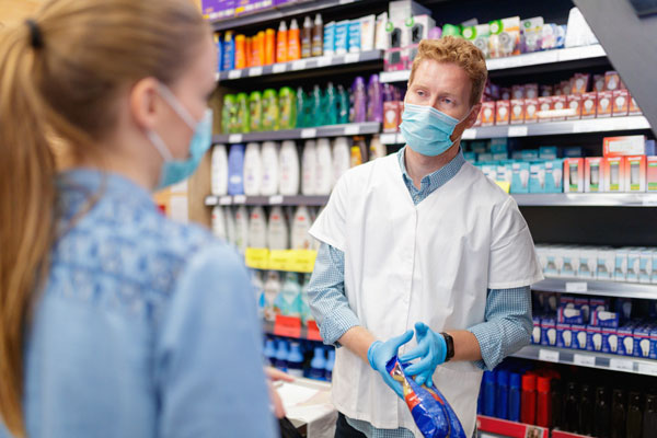 retail worker in mask listening to customer