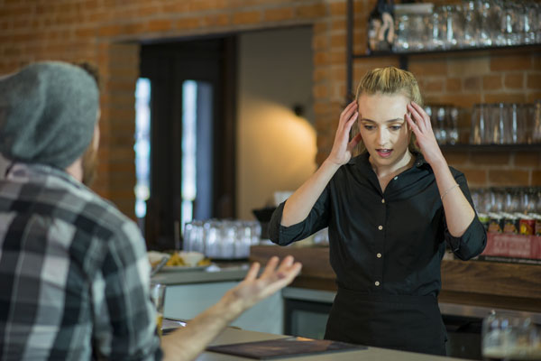 staff member feeling stressed with aggressive customer